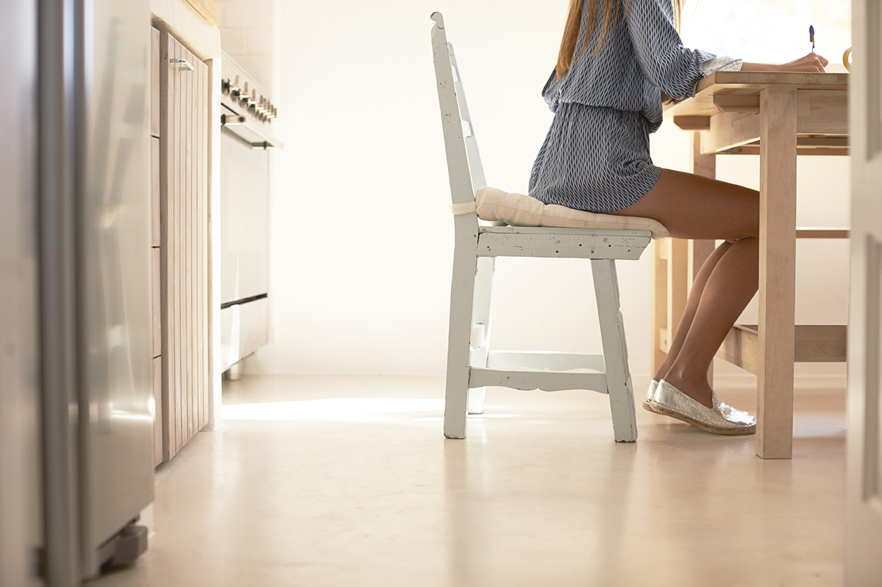 Crop shot of young woman writing at the kitchen table